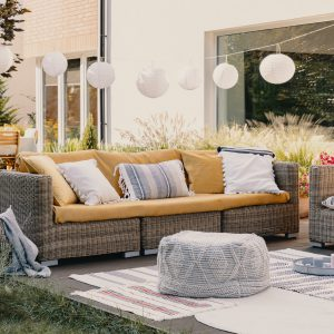 Pouf next to rattan couch and armchair on wooden terrace with flowers and lamps